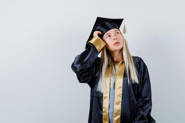 Blondes mädchen, das in denkender pose in abschlusskleid und mütze steht und nachdenklich aussieht