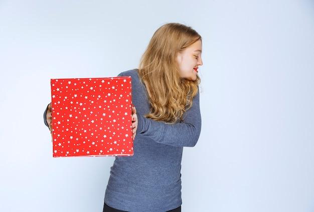 Blondes mädchen, das jemandem eine rote geschenkbox anbietet.