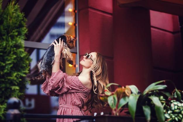 Blondes mädchen, das kleinen hund küsst