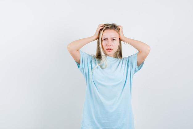 Blondes mädchen, das kopf mit händen im blauen t-shirt umklammert und ernsthafte vorderansicht sieht.