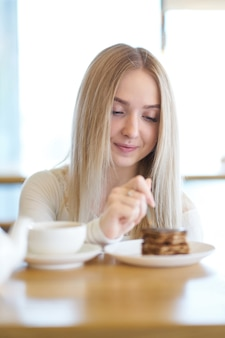 Blondes mädchen, das kuchen im café isst
