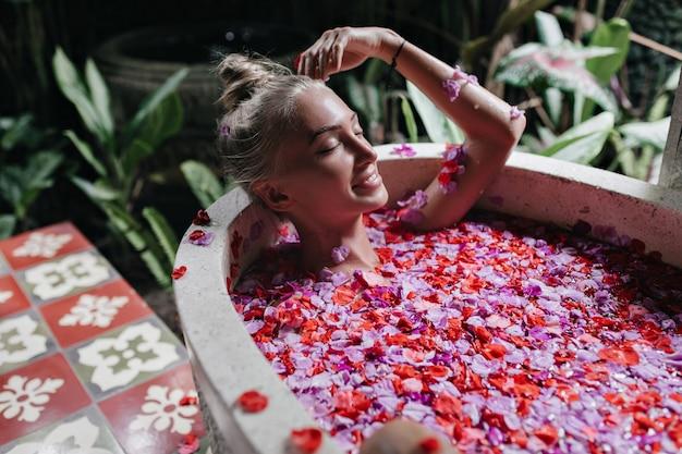 Blondes mädchen, das lächelt, während es im bad kühlt. wunderschöne kaukasische frau, die spaß während spa mit blumen hat.