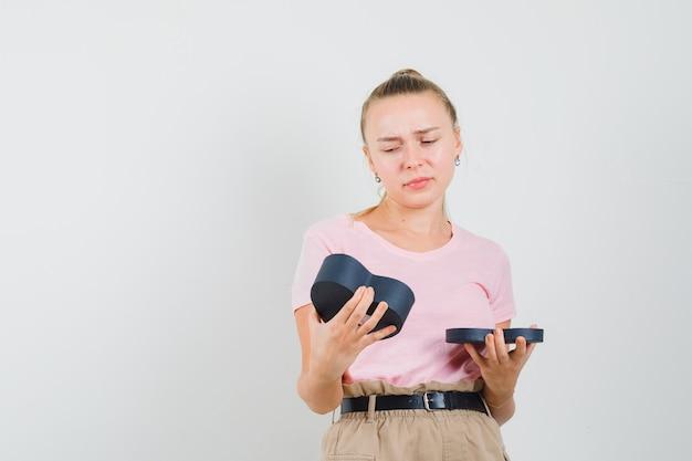 Blondes mädchen, das leere geschenkbox im t-shirt, in den hosen betrachtet und niedergeschlagen schaut, vorderansicht.