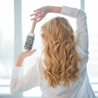 Blondes mädchen, das mit haarbürste aufwirft