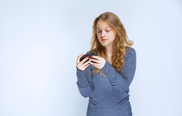 Blondes mädchen, das mit ihrem smartphone sms schreibt und sendet.