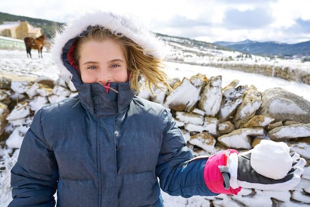 Blondes mädchen, das mit schneeball im winter spielt