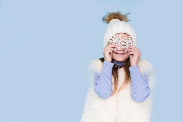 Blondes mädchen, das mit schneeflockenaugen aufwirft