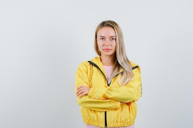 Blondes mädchen, das mit verschränkten armen in gelber jacke steht und selbstbewusst aussieht.