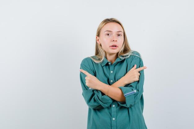 Blondes mädchen, das mit zeigefingern in grüner bluse in entgegengesetzte richtungen zeigt und strahlend aussieht.