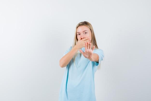 Blondes mädchen, das mund mit hand bedeckt, stoppschild im blauen t-shirt zeigt und überrascht, vorderansicht schaut.