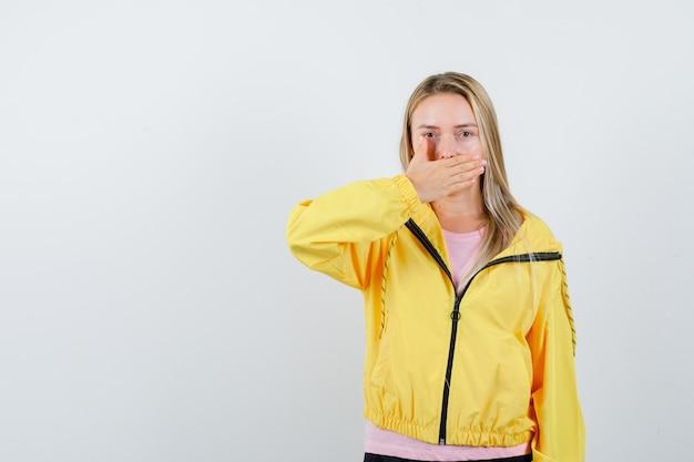 Blondes mädchen, das mund mit hand im rosa t-shirt und in der gelben jacke bedeckt und ernst schaut