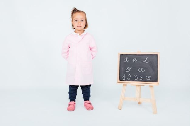 Blondes mädchen, das rosa kinderschürze in der klasse neben tafel auf einem weißen raum trägt