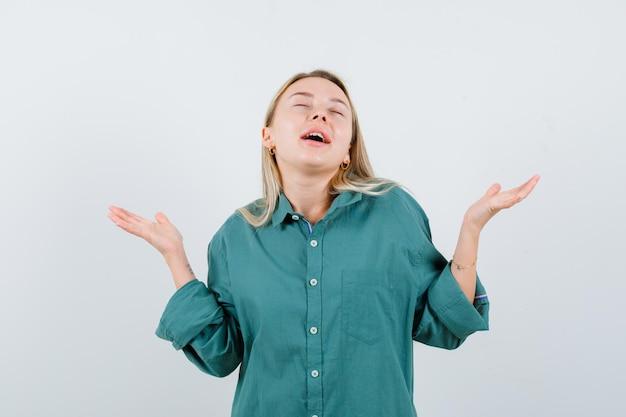 Blondes mädchen, das sich fragend in grüner bluse die hände ausdehnt und glücklich aussieht.