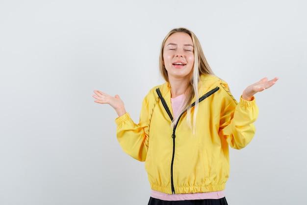 Blondes mädchen, das sich fragend in rosa t-shirt und gelber jacke die hände ausstreckt und verwirrt aussieht.