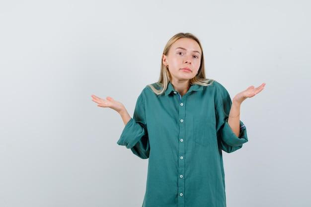 Blondes mädchen, das sich in grüner bluse fragend die hände ausstreckt und verwirrt aussieht
