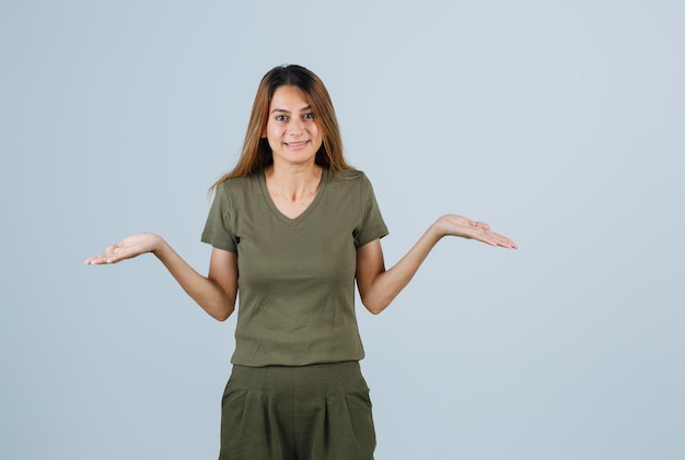Blondes mädchen, das sich in olivgrünem t-shirt und hose fragend die hände ausstreckt und verwirrt aussieht. vorderansicht.