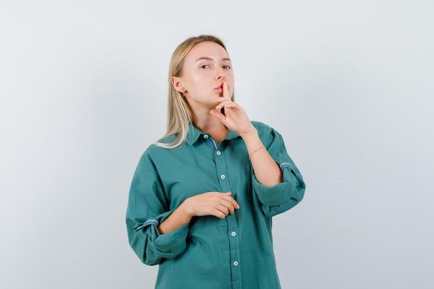 Blondes mädchen, das stillegeste in grüner bluse zeigt und strahlend aussieht