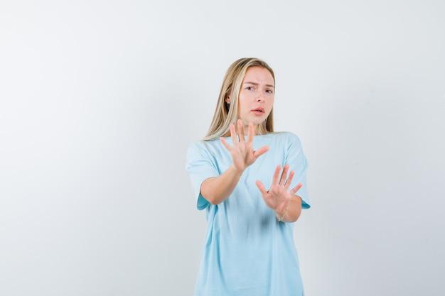 Blondes mädchen, das stoppschilder im blauen t-shirt zeigt und unbequem, vorderansicht schaut.
