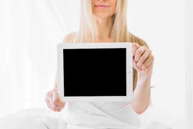 Blondes mädchen, das tablette zeigt