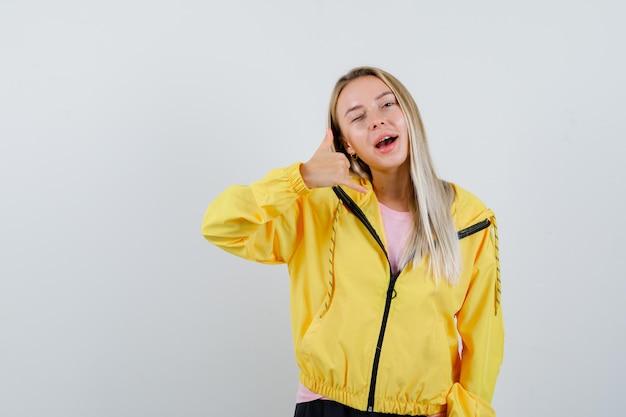 Blondes mädchen, das telefongeste in gelber jacke zeigt und selbstbewusst aussieht.