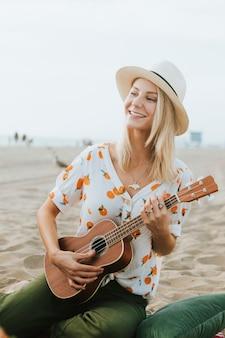 Blondes mädchen, das ukulele für ihre freunde am strand spielt