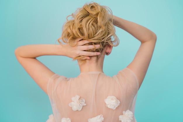 Blondes mädchen, das um ihrem haar sich kümmert