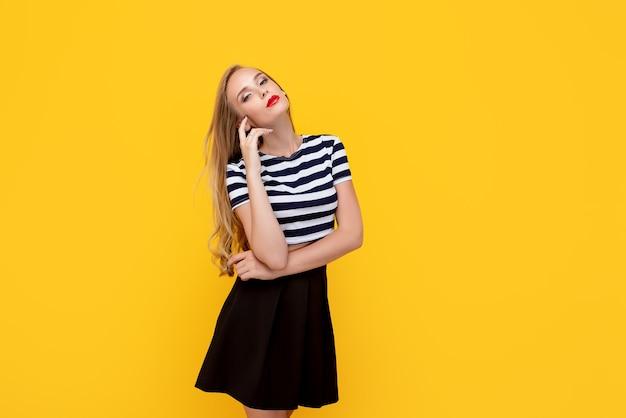 Blondes mädchen, das zur kamera trägt und abgestreiftes t-shirt trägt, das gegen gelbe wand steht