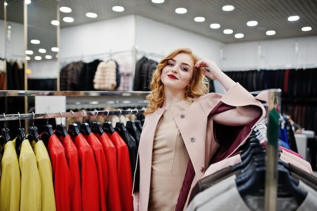 Blondes mädchen der eleganz im mantel im geschäft von pelzmänteln und von lederjacken.