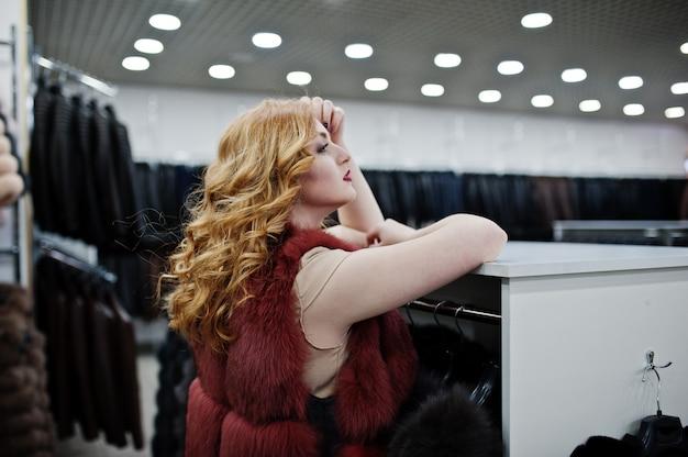 Blondes mädchen der eleganz im pelzmantel im geschäft von pelzmänteln und von lederjacken.