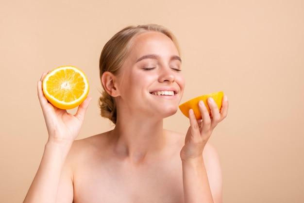 Blondes mädchen der nahaufnahme mit zitrusfrucht- und pfirsichhintergrund