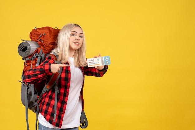 Blondes mädchen der vorderansicht mit ihrem rucksack, der auf ihr ticket zeigt