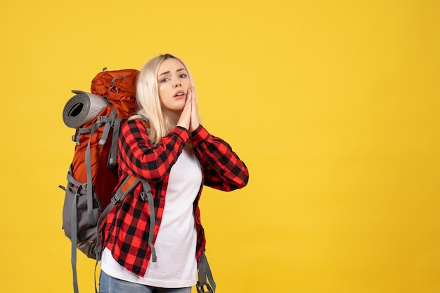 Blondes mädchen der vorderansicht mit ihrem rucksack, der hände zusammen verbindet