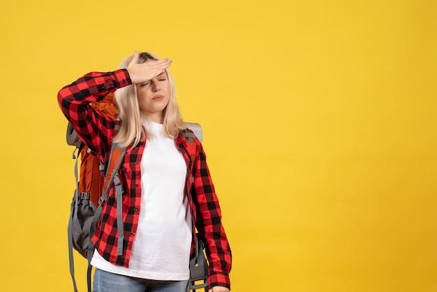 Blondes mädchen der vorderansicht mit ihrem rucksack, der hand auf ihre stirn legt