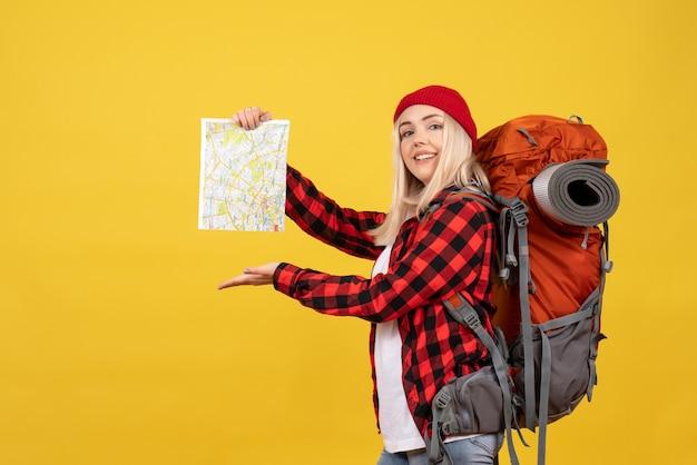 Blondes mädchen der vorderansicht mit ihrem rucksack, der karte hält