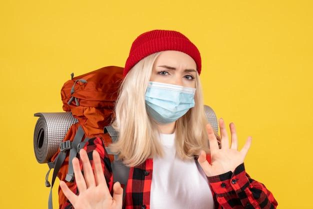 Blondes mädchen der vorderansicht mit ihrem rucksack, der maske trägt