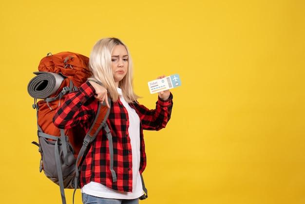 Blondes mädchen der vorderansicht mit ihrem rucksack, der ticket hält, das auf sich zeigt