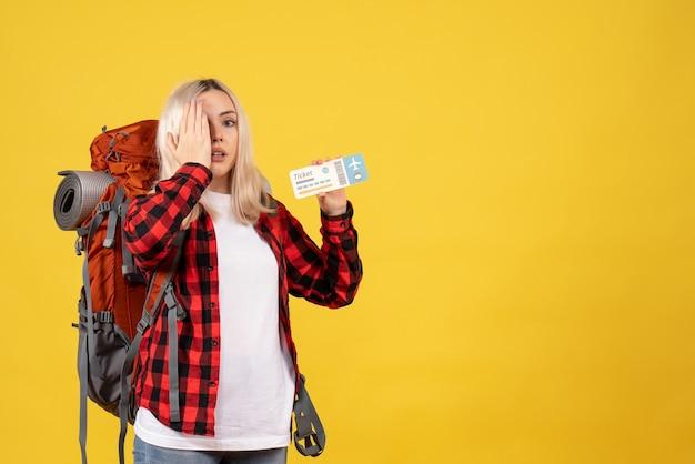 Blondes mädchen der vorderansicht mit ihrem rucksack, der ticket hält hand auf ihr auge hält
