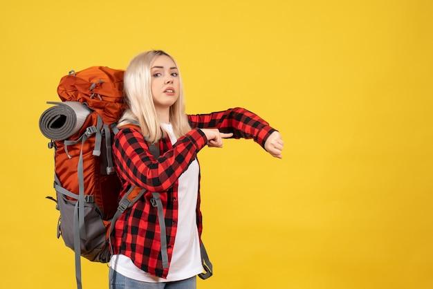 Blondes mädchen der vorderansicht mit ihrem rucksack, der zeit fragt Kostenlose Fotos