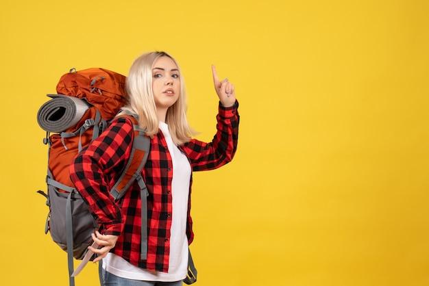 Blondes mädchen der vorderansicht mit ihrem rucksack, der zur decke zeigt Kostenlose Fotos