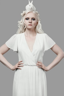 Blondes mädchen des albinos im eleganten kleid, das mit nettem kleinem kaninchen aufwirft