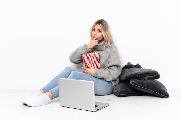 Blondes mädchen des jugendlichen, das popcorn beim aufpassen eines films auf dem laptop hat zweifel und mit verwirrt gesichtsausdruck isst