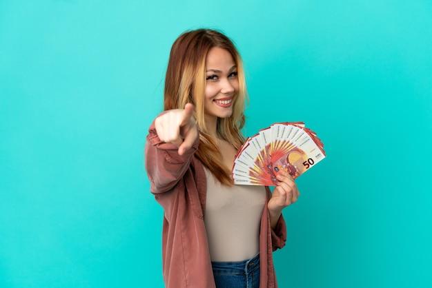 Blondes mädchen des teenagers, das eine menge euro über isoliertem blauem hintergrund nimmt, zeigt mit einem selbstbewussten ausdruck mit dem finger auf sie