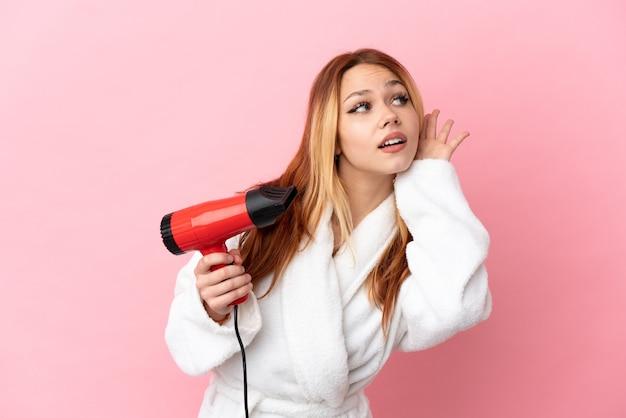 Blondes mädchen des teenagers, das einen haartrockner über lokalisiertem rosa hintergrund hält und etwas hört, indem es die hand auf das ohr legt