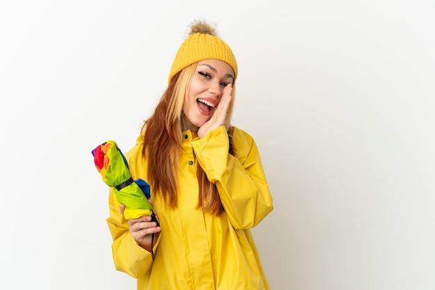 Blondes mädchen des teenagers, das einen regendichten mantel über isoliertem weißem hintergrund trägt und mit weit geöffnetem mund schreit