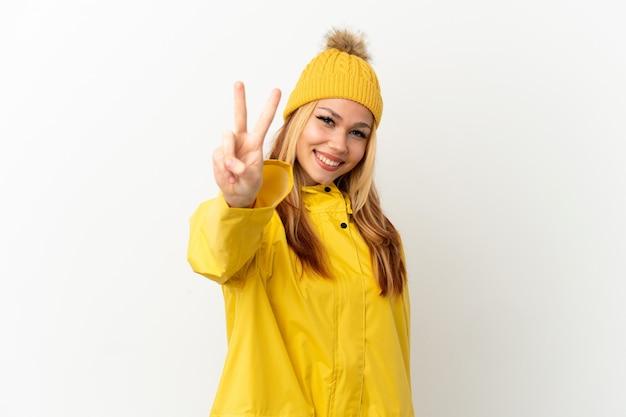 Blondes mädchen des teenagers, das einen regendichten mantel über lokalisiertem weißem hintergrund trägt, lächelt und zeigt victory-zeichen