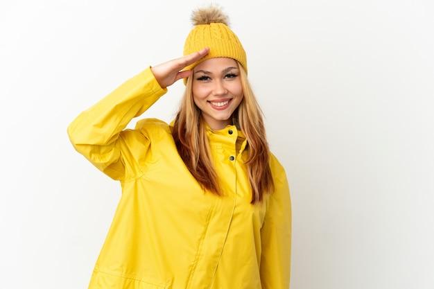 Blondes mädchen des teenagers, das einen regendichten mantel über lokalisiertem weißem hintergrund trägt und mit der hand mit glücklichem ausdruck grüßt