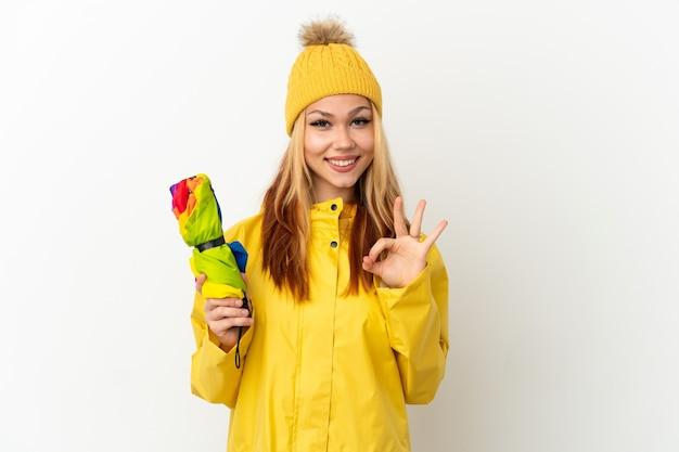 Blondes mädchen des teenagers, das einen regenfesten mantel über lokalisiertem weißem hintergrund trägt, der okayzeichen mit zwei händen zeigt Premium Fotos