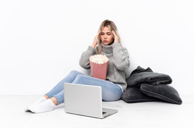 Blondes mädchen des teenagers, das popcorn isst, während man einen film auf dem laptop mit kopfschmerzen sieht