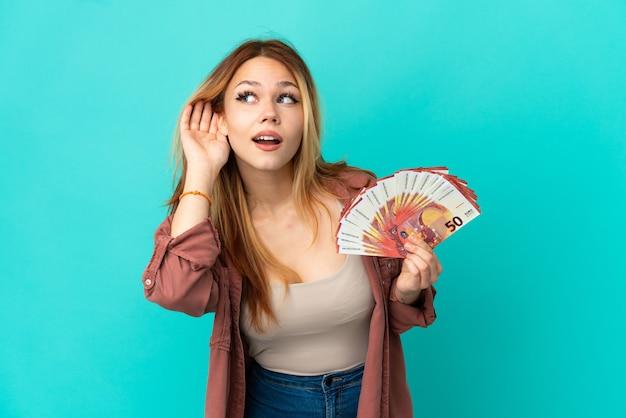 Blondes mädchen des teenagers, das viel euro über isolierte blaue wand nimmt und etwas hört, indem es die hand auf das ohr legt