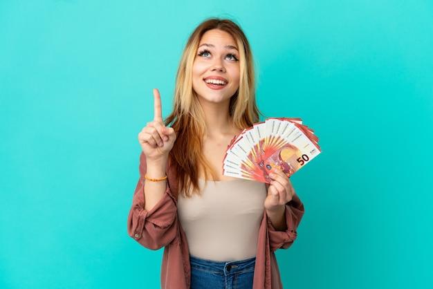 Blondes mädchen des teenagers, das viel euro über isoliertem blauem hintergrund nimmt, der nach oben zeigt und überrascht